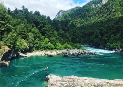 rivière au chili avec un kayakiste rouge au milieu d'une rivière avec de la forêt autour